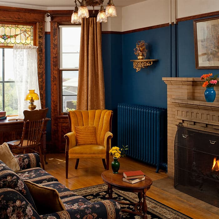 Sitting Room with couch, desk, yellow chair, and fireplace