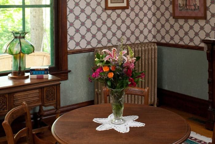Dining table set with flowers and ornate radiator in background