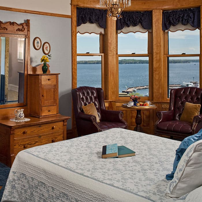 Tower Room with bed, two leather chairs and view from windows
