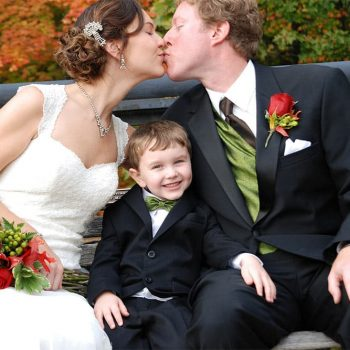 Bride and Groom kiss on bench with young boy between them