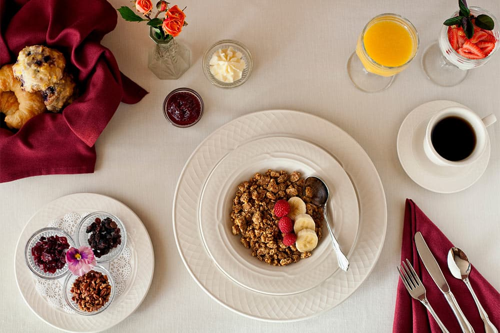 Breakfast table set with Granola bowl in the middle