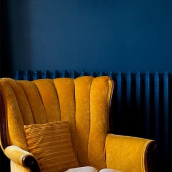 Yellow reading chair with an open book in Master Suite