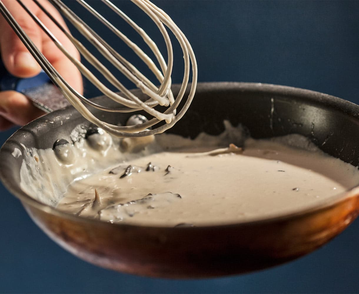 Chef holding whisk and pan of fresh sauce